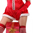 Girl dressed as Santa with a gift - Stock Photo