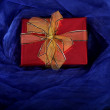 Red gift on a blue background — Stock Photo