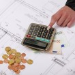 Hands with house construction plan, calculator, money, coins - Stock Photo