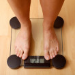 Girl standing on the scales - Stock Photo