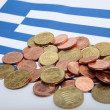 Wrinkled Greek flag burried under Euro coins against a white background - Stock Photo