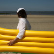 Woman with yellow mattress on the beach — Stockfoto