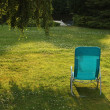 Simple chaise lounge on the green grass - Stock Photo