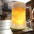 Glass of beer on a wooden table - ストック写真