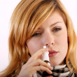 Spraying nose spray - Stock Photo