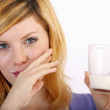 Beautiful blond woman with a glass of milk — Stock Photo