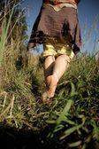 Girl running barefoot on grass — Stock Photo