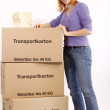 Young woman with moving box and books - Stock Photo