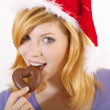 Young woman with santa hat and gingerbread (white background) - Stock Photo
