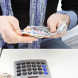 Hands with money and calculator — Stock Photo #16625413