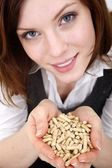 Young beautiful woman with wood pellets — Stock Photo