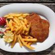 Wiener Schnitzel with chips and garnish — Stock Photo