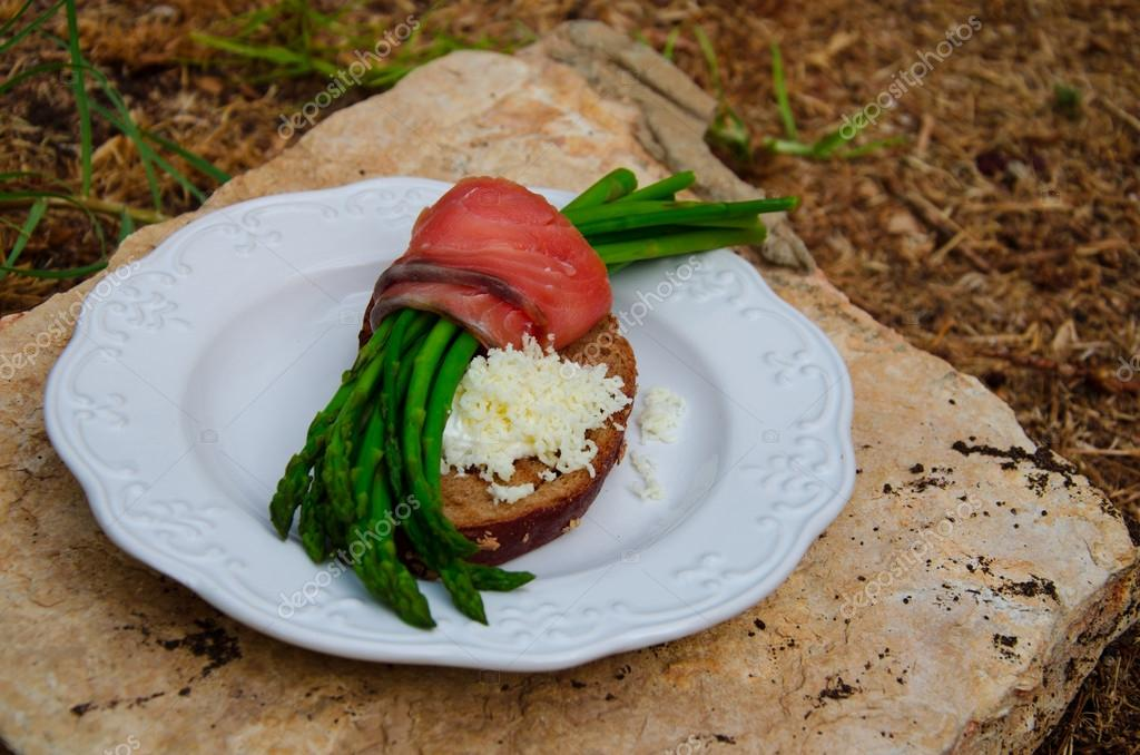 Asparagus, Rye Bread toasted, goat cream-cheese and grated Montenegro goat cheese on a plate and white stone — Stock Photo #13856367