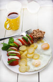 Breakfast: Fried Eggs, New Potatoes And Caprese Salad. — Stock Photo