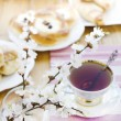 Cheese and raisins buns, cup of Tea and blossoming apricot in the vase. — Stock Photo