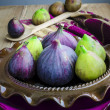 Purple and green Figs on the ceramic plate — Stock Photo