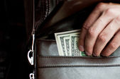 100 dollar bills and a leather bag — Stock Photo