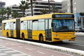 A yellow bus circulating — Stock Photo