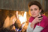 Lady, wine, fireplace — Stock Photo