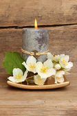 Candle and white flowers — Stock Photo