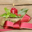 Red ribbon bow and yule log — Stock Photo