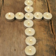 Candles form a cross on wood - Stok fotoğraf