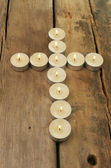 Candles form a cross on wood — Stockfoto