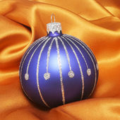 Christmas ball on gold cloth — Stockfoto