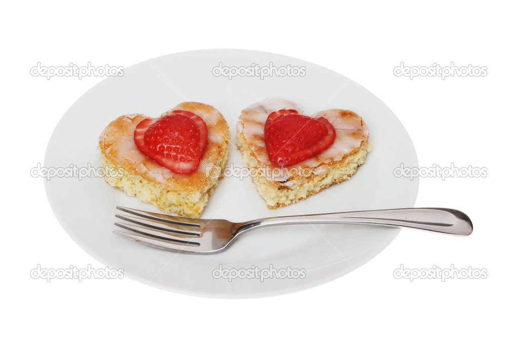 Two heart shaped cakes with a fork on a plate isolated against white  Stock Photo #18823917