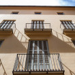 Balconies and windows illuminated with the light of noon - Stock Photo