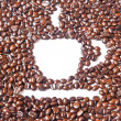 White coffee cup in many brown coffee beans for background — Stok fotoğraf