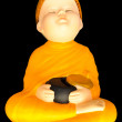 Doll clay baby monk meditation with  alms bowl isolated on black — Stockfoto