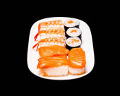 Sushi in white plate on black background — Stock Photo