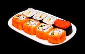 Sushi in weißen teller auf schwarzem hintergrund — Stockfoto