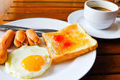Breakfast with fried eggs,sausage, toasts and coffee — Stock Photo