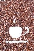 Xícara de café branca em muitos feijões de café marrons para plano de fundo — Foto Stock
