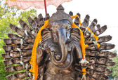 Many cast bronze hands of god Ganesha with yellow garland. — Stock Photo