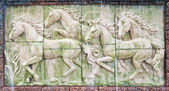 Horses in low relief statue cut out as jig saw image and water f — Stock Photo