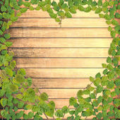 Green creeper plant shaped as heart on wood plank  — Zdjęcie stockowe