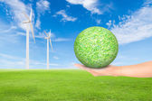 Green grass field with wind turbine and hand holding green grass — Foto Stock