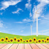 Sunflowers with wind turbine on green grass field against blue s — Photo