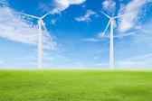 Wind turbine on green grass with blue sky — Stock Photo