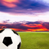 Soccer ball with green grass field against sunset sky — Stock Photo