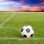 Soccer ball on soccer field against sunset sky  — Zdjęcie stockowe