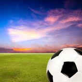 Piłka piłka nożna pole trawa zielona, przed zachodem słońca niebo — Zdjęcie stockowe