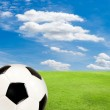 Soccer ball with green grass field against blue sky — Stock Photo #47466447
