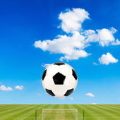 Soccer ball with soccer field against  blue sky background — Stock Photo