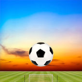 Soccer ball with soccer field against beautiful sunset — Stock Photo