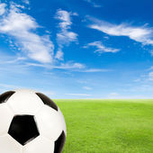 Soccer ball with green grass field against blue sky — Stock Photo