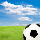 Soccer ball with green grass field against blue sky — 图库照片